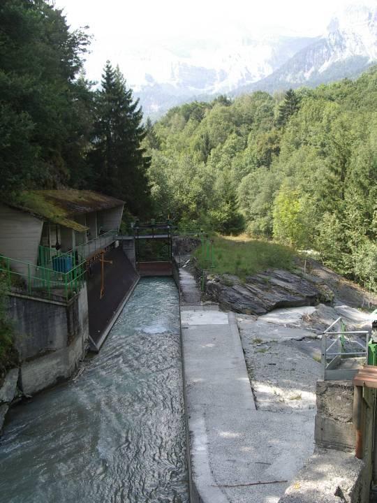 Grille de la prise d'eau du barrage vue depuis la passerelle ; on voit nettement la masse rocheuse sur laquelle le barrage prend appui