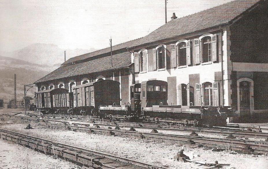 Des wagons plats automoteurs stationnent avec trois wagons sur trucks-porteurs le long du dépôt de St-Gervais-le Fayet (J.P. Gide et J. Banaudo, Les trains du Mont-Blanc)