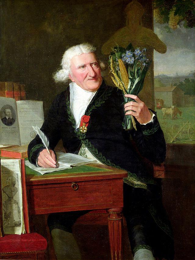 Portrait d'Antoine Parmentier en 1812 par François Dumont, dit Dumont aîné (1751-1831). Parmentier est assis dans son cabinet, en habit d'académicien, et tient un bouquet de toutes les plantes qu'il a étudiées.