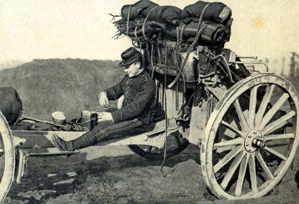 Photo datant de 1914 montrant un artilleur pendant la pause. Assis sur la flèche du canon de 75, il est en train de moudre son café à l'aide du petit moulin réglementaire. Nous pouvons voir sur cette photo l'avant-train avec son chargement complet