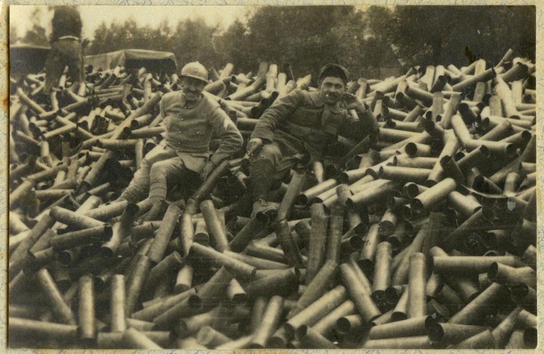 Deux soldats du 14e escadron du train assis sur un tas de douilles de 75 mm en 1915 (Site archives.ecpad)