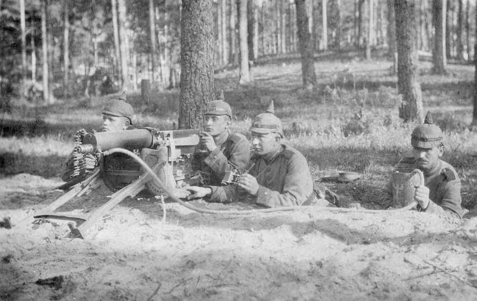 Mitrailleuse MG 08 en position, prête à faire feu. Nous sommes très probablement avant-guerre ; les hommes portent la tenue modèle 1895 et la mitrailleuse ne possède pas de rail pour fixer la lunette (modification de 1912). Le tuyau d'échappement de la vapeur d'eau est très nettement visible ; l'homme à droite en maintient l'extrémité dans le bidon cylindrique à eau. (site mitrailleuse.fr)
