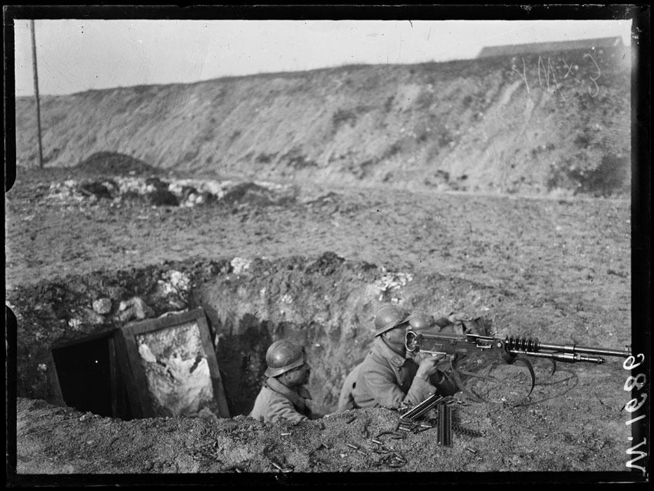 Mitrailleuse Hotchkiss sur affût berceau dans un trou d'obus (école des mitrailleuses, près de Châlons-sur-Marne) ; au premier plan, les chargeurs en bandes rigides.