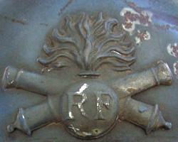 Attribut du casque Adrian d'artillerie : grenade brochant sur deux canons croisés (site world-war-helmets.com)