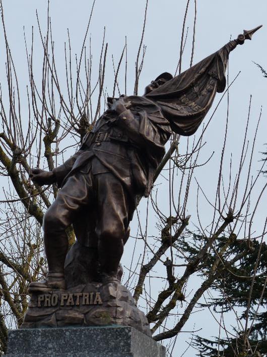 Statue en bronze du monument aux morts d'Uxegney, Vosges, Poilu mourant défendant son drapeau, avec fer de lance et inscriptions sur le drapeau (« Honneur… »), PRO PATRIA (site monumentsmorts.univ-lille3.fr)