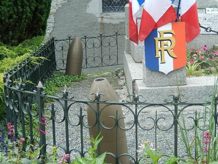 Quatre obus d'artillerie lourde (diamètre extérieur 260 mm) sont placés aux 4 coins du monument aux morts de Passy, à l'intérieur du ban (cliché Bernard Théry, octobre 2015)